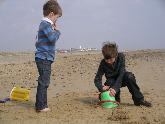Serious sandcastle building, with Southwold town and lighthouse in the background